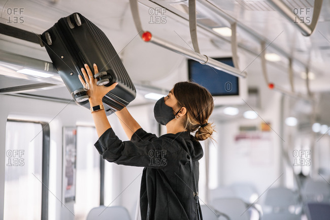 Woman in mask putting suitcase on shelf