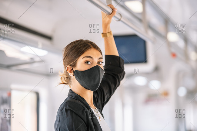 Successful woman with black suit and mask travels by train