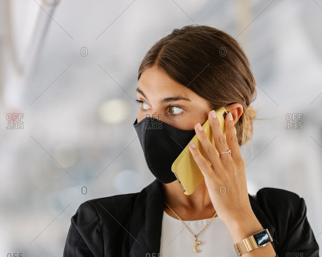 Businesswoman answering phone call while commuting to work