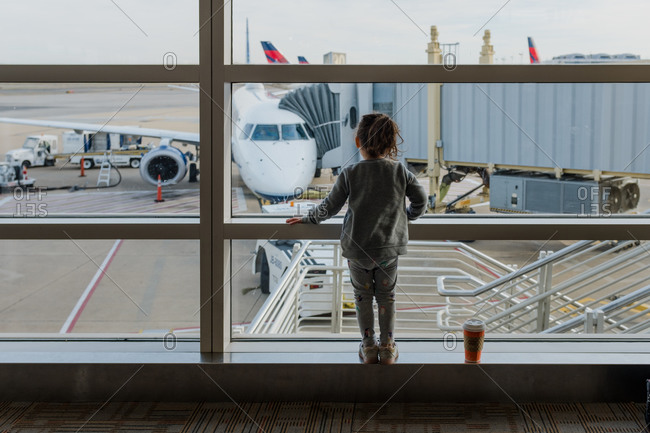 Little girl watches plane docked to jet bridge