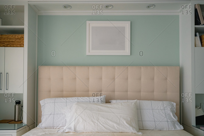 Headboard and custom built in shelving in clean modern bedroom