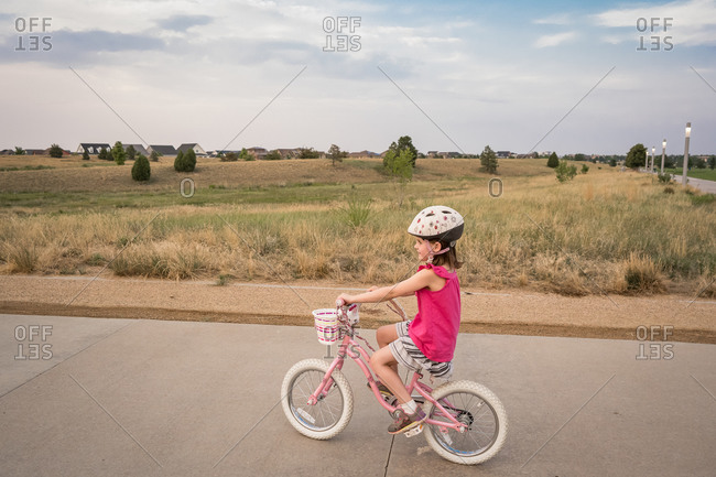 Smiling young girl rides through a neighborhood park in the evening