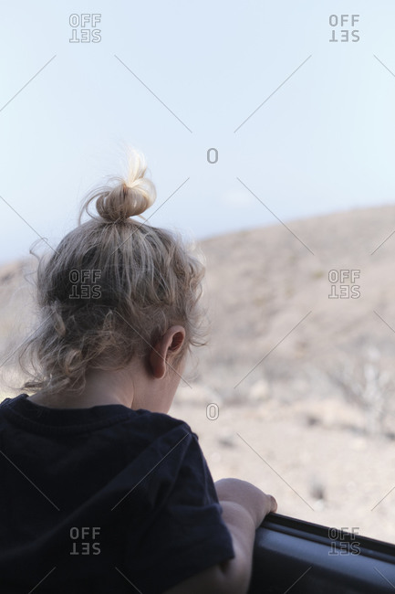 Back of a blonde child looking out the window of a car