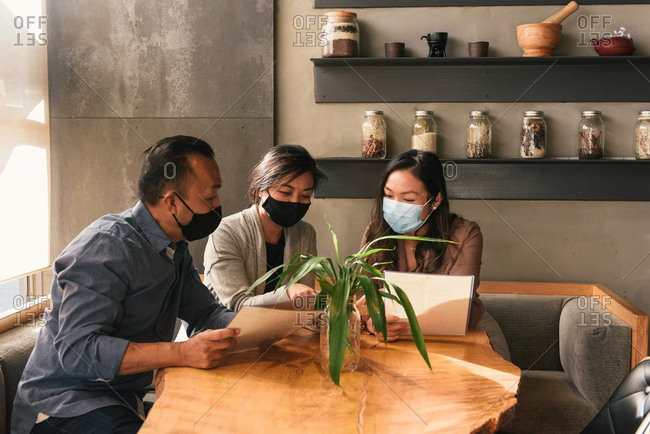 Masked up friends looking over menus in booth at stylish restaurant