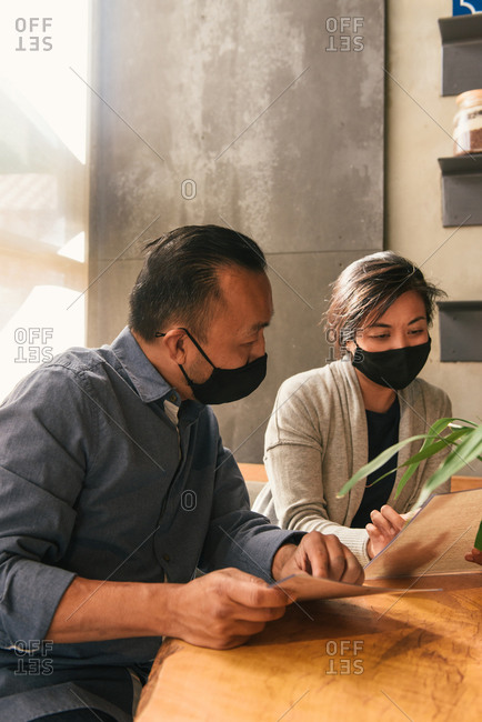 Husband and wife wearing masks and looking over menu for indoor dining