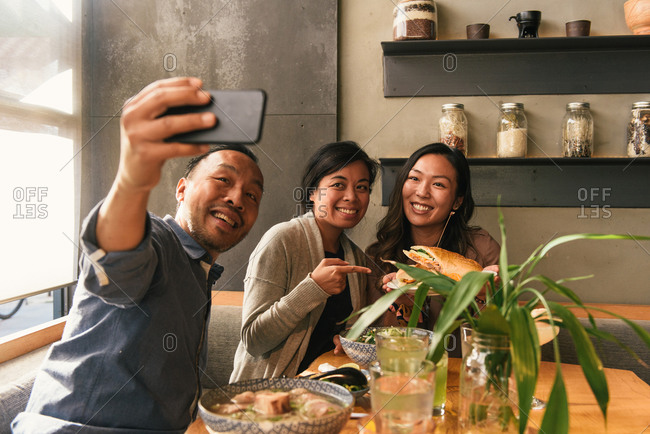 Man taking selfie of groups of friends holding up food at a restaurant