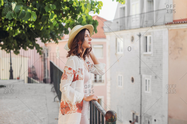 Young woman in a straw hat looking dreamy, Lisbon streets