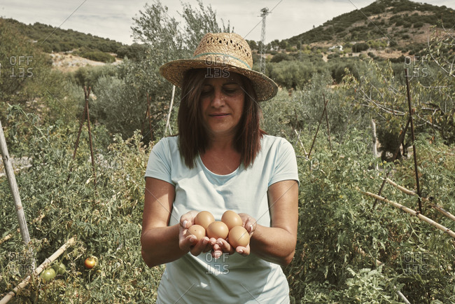 A woman with eggs in her hands collected from her own farm
