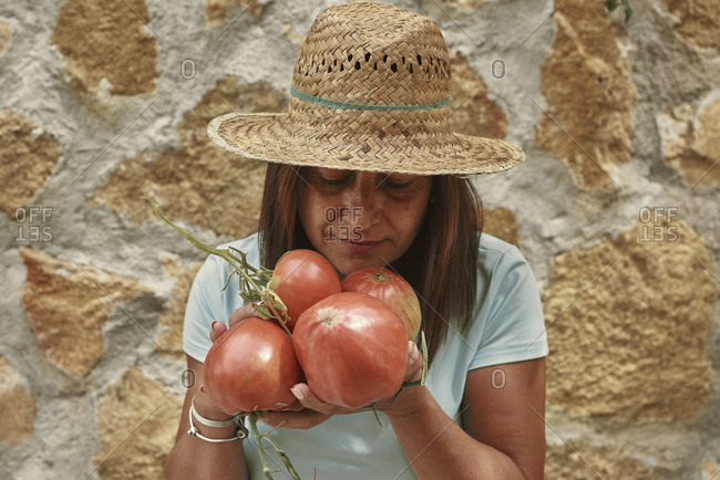 A woman smelling tomatoes picked from her own garden
