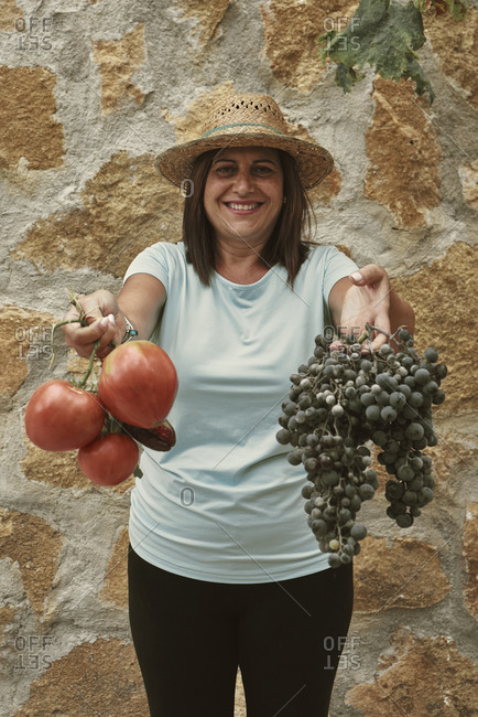 A smiling woman shows the products from her orchard