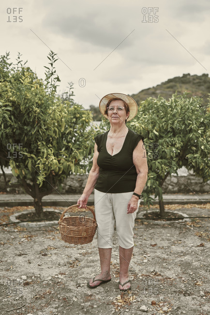 Portrait of an old lady with hat and basket in her small orchard