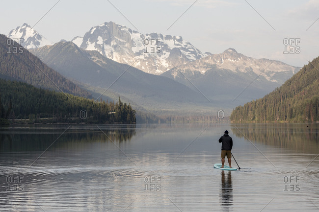 Back view of anonymous male on paddleboard on calm surface of Duffey lake and enjoying landscape of mountains in morning in British Columbia