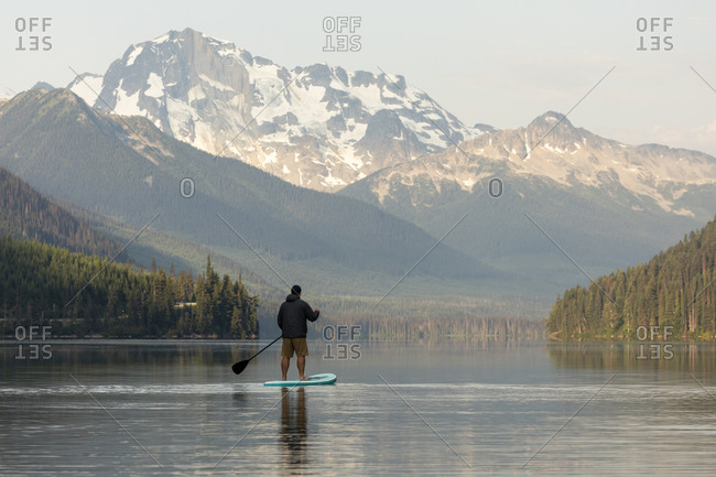 Man on paddle board on calm Duffey Lake in mountains at sunrise.