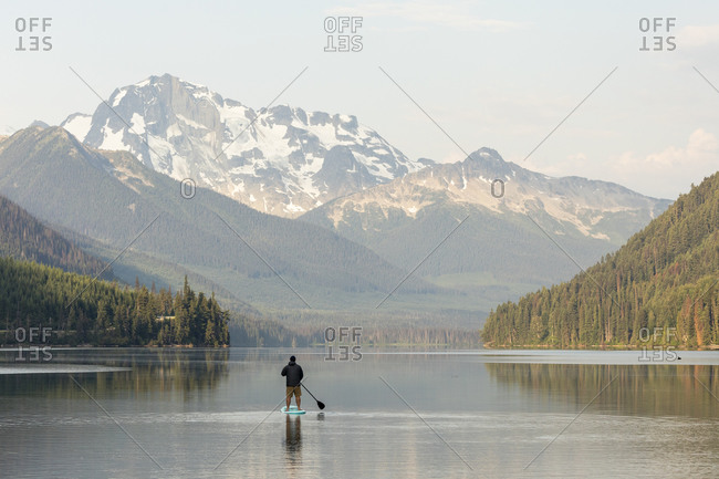 Man on paddle board on calm lake backed by mountains at sunrise in BC