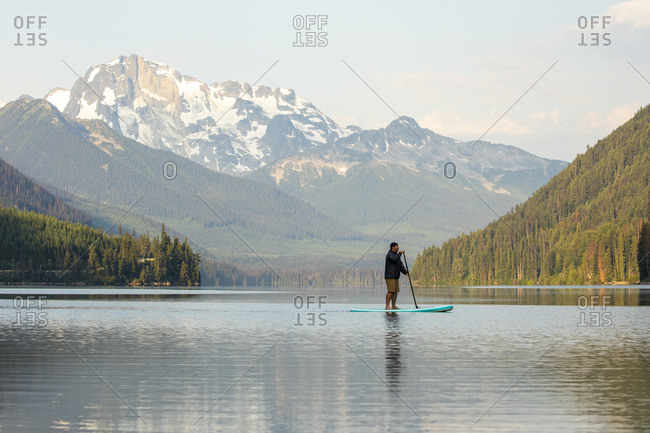 Side view of male on paddle board Duffey Lake on background of spectacular mountain ridge in morning in British Columbia