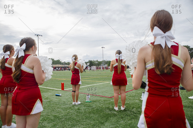 Columbus, OH, United States - August 28, 2020: A group of cheerleaders with bows in hair stand on football field