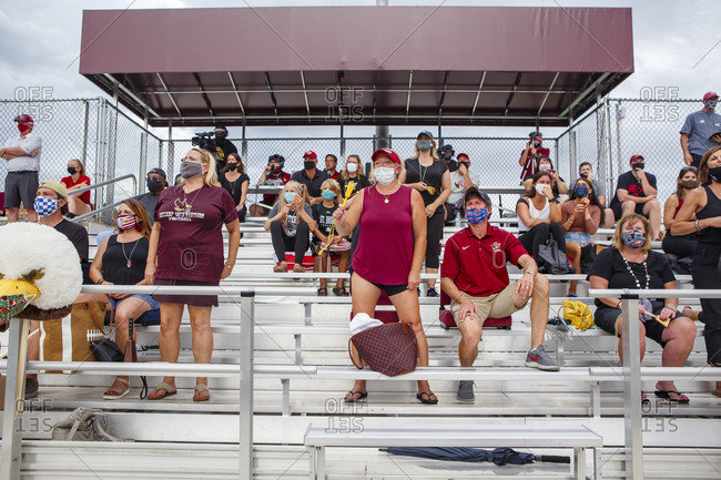 Columbus, OH, United States - August 28, 2020: A group of masked spectators cheer on a football team from bleachers