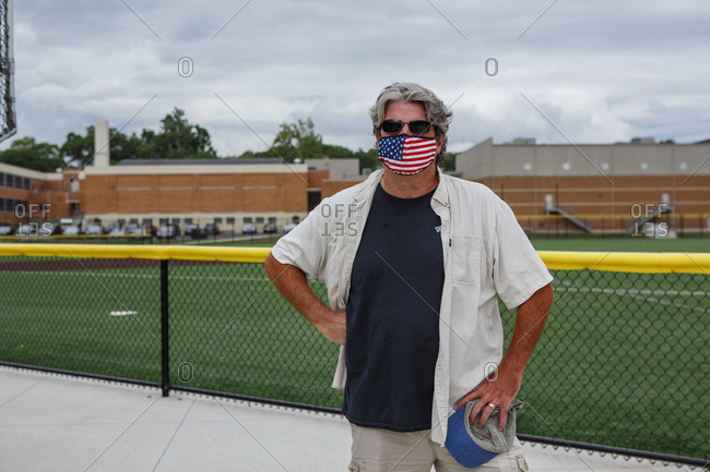 Columbus, OH, United States - August 28, 2020: An older man stands in front of chain link fence wearing a flag mask