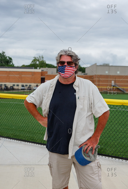 Columbus, OH, United States - August 28, 2020: Top half of man wearing an American Flag mask outside of High School