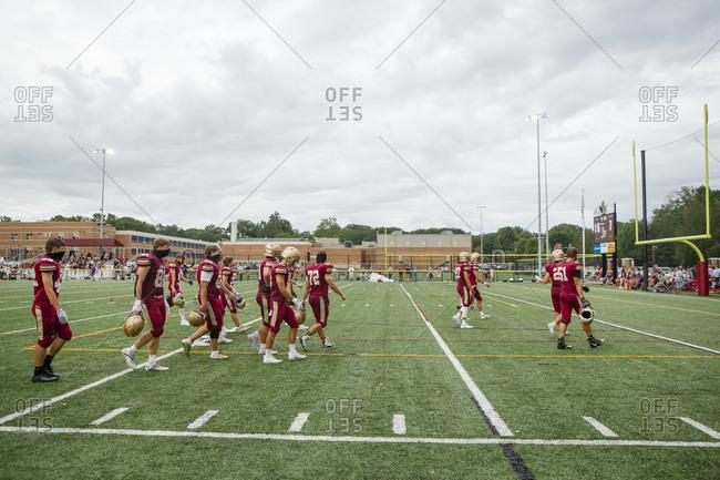 Columbus, OH, United States - August 28, 2020: A high school football team walk across field against cloudy sky