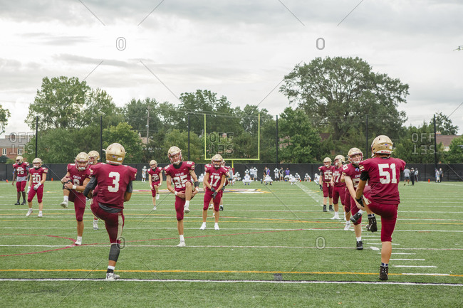 Columbus, OH, United States - August 28, 2020: a team of high school players warm up on a football field in uniform