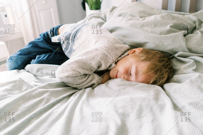 Little boy smushing his face into the soft and cozy blanket on the bed