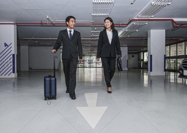 Business couple walking through modern parking lot in Bangkok