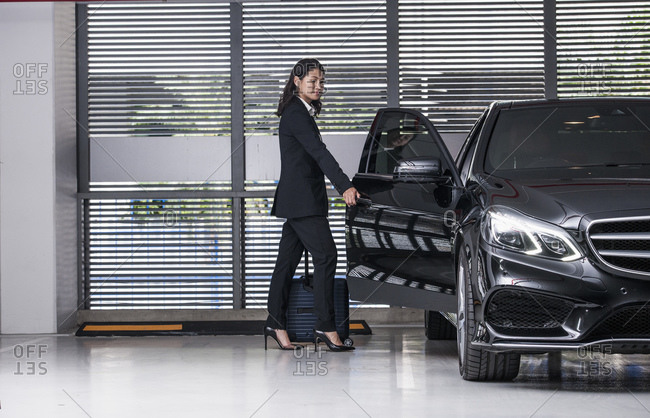 Business woman getting into her luxury car at modern parking lot