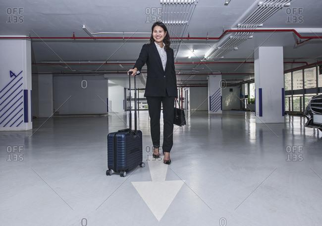 Business woman walking through modern parking lot in Bangkok