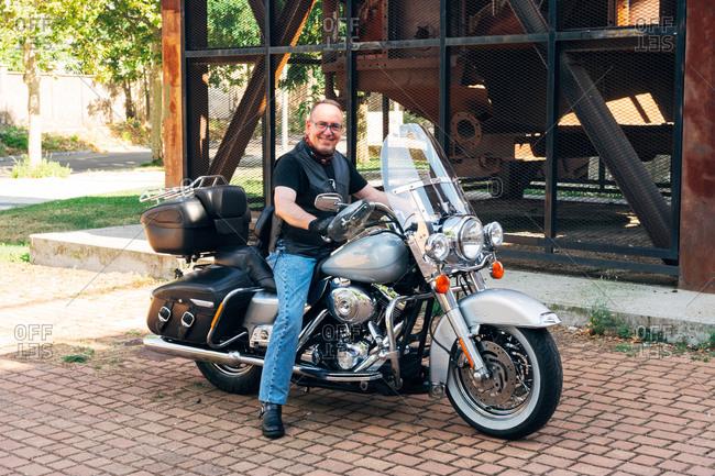 Biker posing smiling on his custom motorcycle