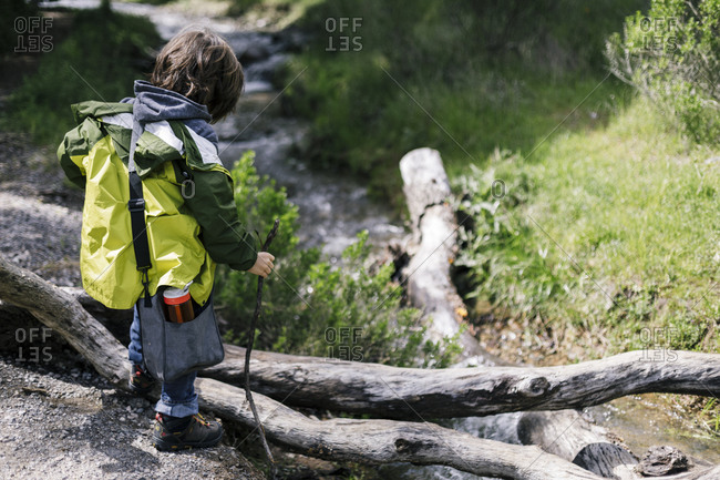 Back of kid looking river wearing raincoats, lunch bag, water bottle