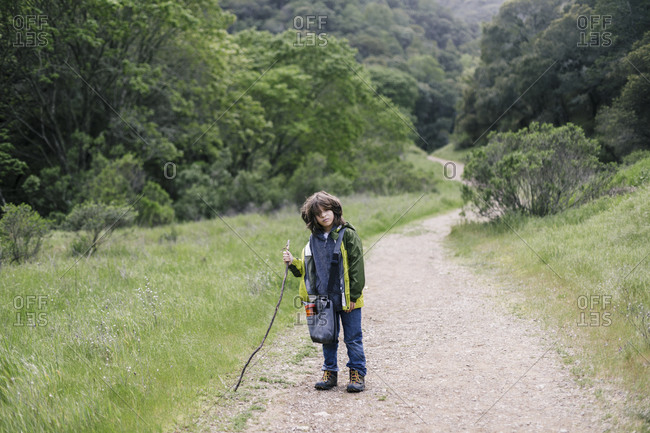 Serious boy with walking stick by tail path on natural park