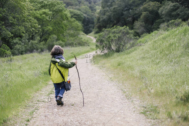 Back view of child walking stick by path trail in nature