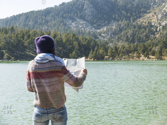 hiker woman looking at map while standing in front of a lake in natural environment and thinking of where to go next