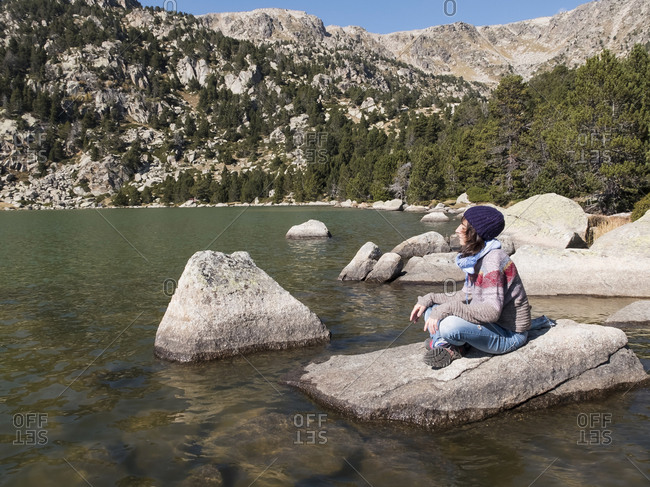 Side view of a young woman sitting on rock while meditating at a mountain lake