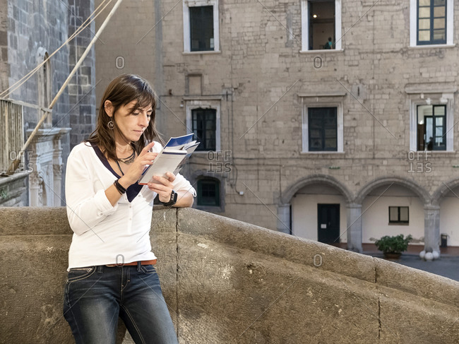 Tourist woman reading guide book in city