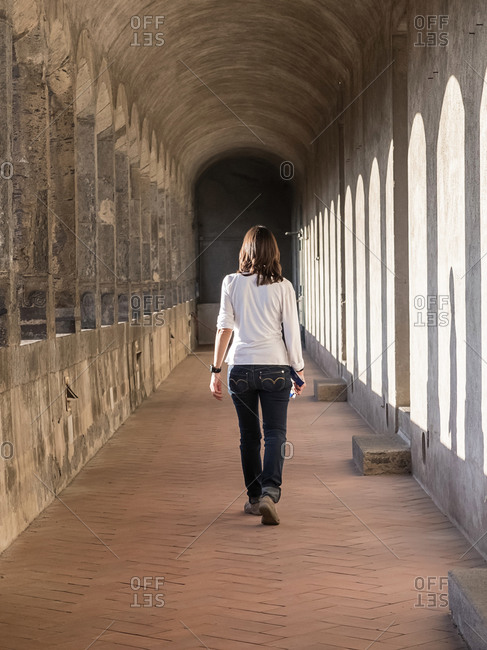 Back view of a traveler girl walking on city street