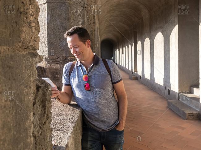 Portrait of handsome traveler man using his mobile.