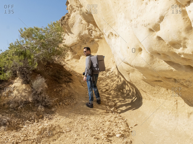 Professional photographer with backpack and sunglasses against big rock