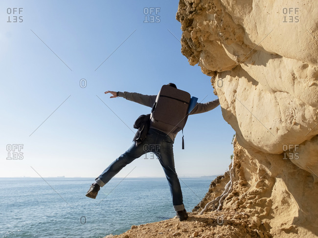 Professional photographer with backpack on a rock path over sea