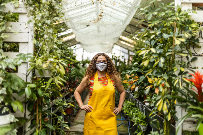 Young blonde adult woman with curly hair and a yellow apron wearing a face mask in garden shed and posing