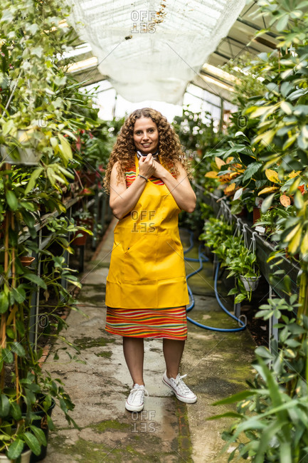 Young blonde adult woman with curly hair and a yellow apron working her garden shed, taking off the mask and smiling