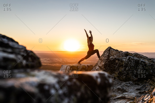 Young yogi woman practicing yoga on a rock in the mountain with the light of sunrise, side view with one leg on a rock and arms raised