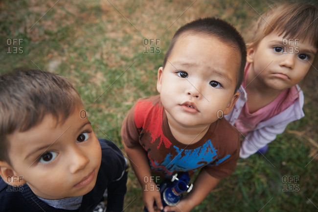 Three cute kids standing on a grass and looking at camera