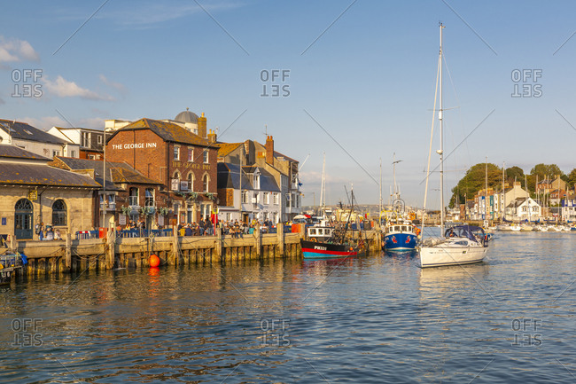 September 10, 2020: View of boats in the Old Harbor and quayside houses at sunset, Weymouth, Dorset, England, United Kingdom, Europe