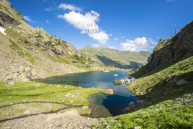 Elevated view of tents in the green meadows on shores of lake Zancone, Orobie Alps, Valgerola, Valtellina, Lombardy, Italy, Europe