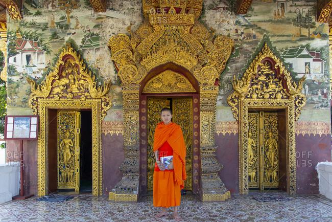 November 26, 2014: A Buddhist monk in saffron robes standing at the Royal Palace, Luang Prabang, Laos, Indochina, Southeast Asia, Asia