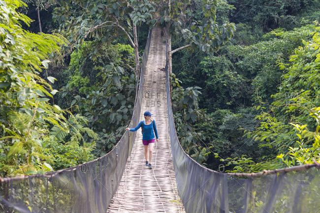 November 27, 2014: A woman crosses a precarious looking suspension bridge over the jungle in Laos, Indochina, Southeast Asia, Asia