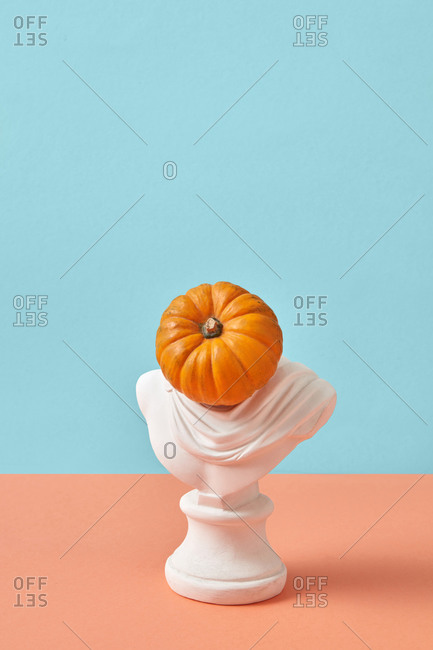 Gypsum sculpture with head in the shape of fresh ripe natural pumpkin on a pastel duotone background with copy space. Halloween concept.