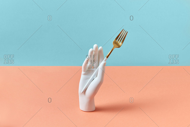 Vertically standing plastic mannequin hand holds metal golden fork on a duotone pastel background with soft shadow, copy space.